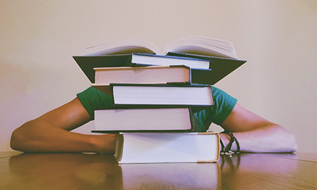 Student sitting behind a stack of books