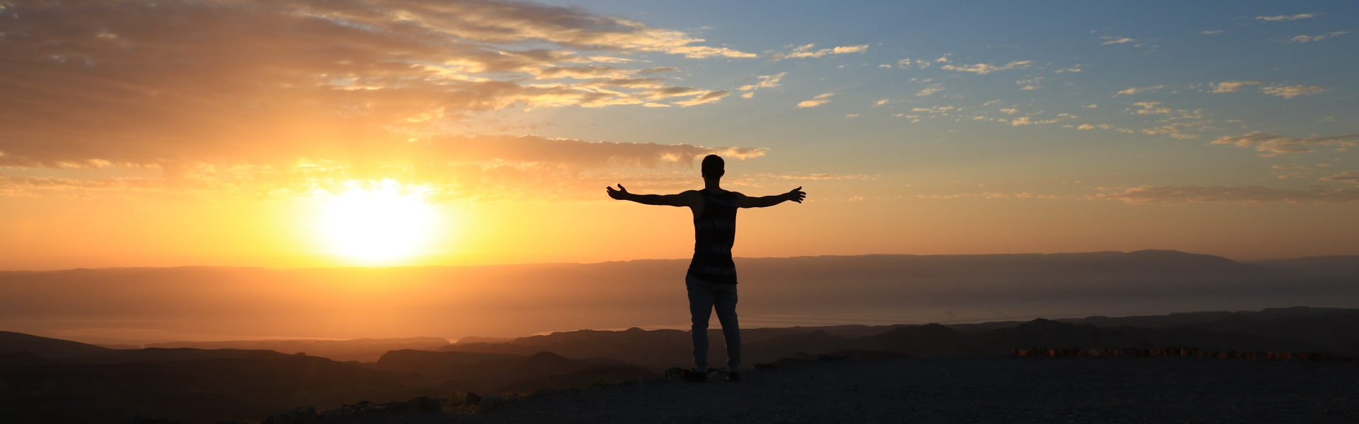 Person standing with outstretched arms at sunset